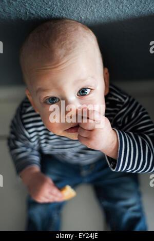 Overhead portrait of baby boy sitting on floor - Stock Photo