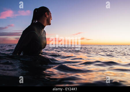 Female surfer wading in sea at sunset, Cardiff-By-The-Sea, California, USA - Stock Photo