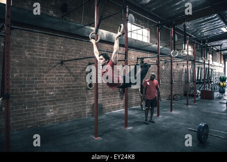 Young man swinging on gym rings in gym - Stock Photo