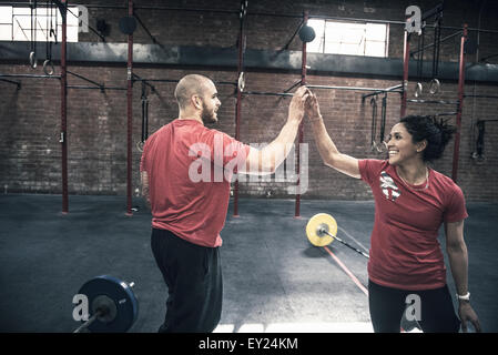 Young man and woman giving each other high five in gym - Stock Photo