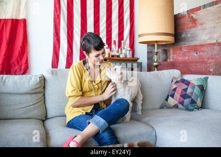 Young woman petting dog on living room sofa - Stock Photo