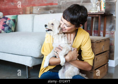 Young woman hugging dog on living room floor - Stock Photo