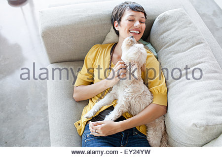 Young woman hugging dog on living room sofa - Stock Photo