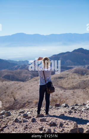 Young woman standing on rocks, looking at mountain view, rear view - Stock Photo