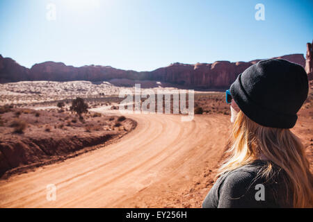 Mid adult woman looking out at rural dirt road, Monument Valley, Utah, USA - Stock Photo