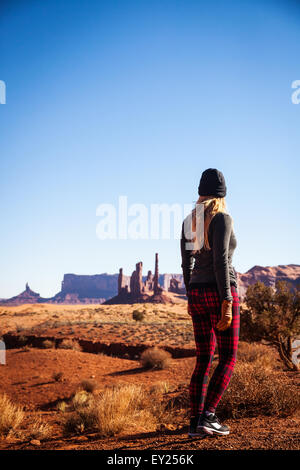 Rear view of mid adult woman looking out at Monument Valley, Utah, USA - Stock Photo
