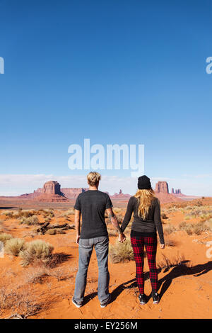 Rear view of tourist couple holding hands, Monument Valley, Utah, USA - Stock Photo