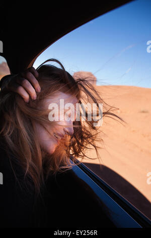 Woman with windswept hair at car window, Monument Valley, Utah, USA - Stock Photo