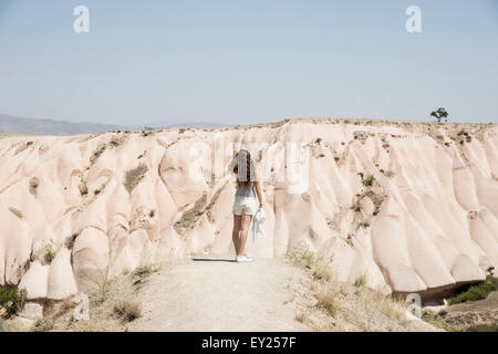 Rear view of female tourist looking out at rock formations, Cappadocia, Anatolia, Turkey - Stock Photo