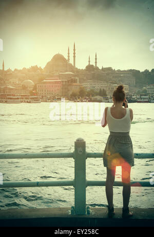 Rear view of female tourist photographing the Bosphorus and Hagia Sophia church, Istanbul, Turkey - Stock Photo