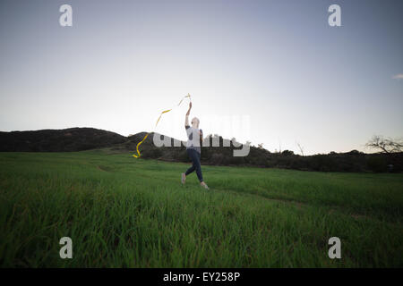 Young woman running in field holding up dance ribbon - Stock Photo