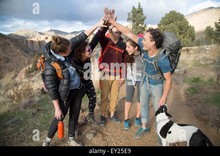 Hikers doing high five, Smith Rock State Park, Oregon, US - Stock Photo