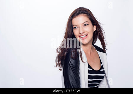 Studio portrait of young woman with long dark hair, smiling - Stock Photo