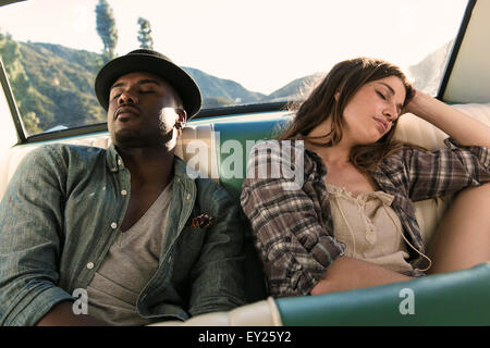 Couple asleep in back seat of car - Stock Photo
