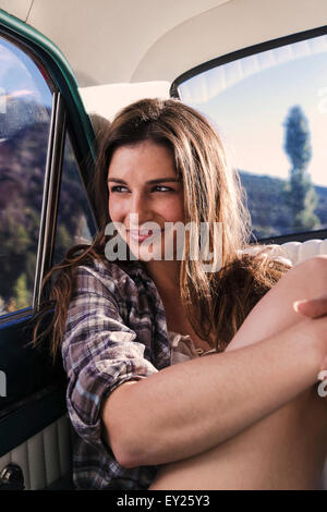Portrait of young woman in back seat of car - Stock Photo