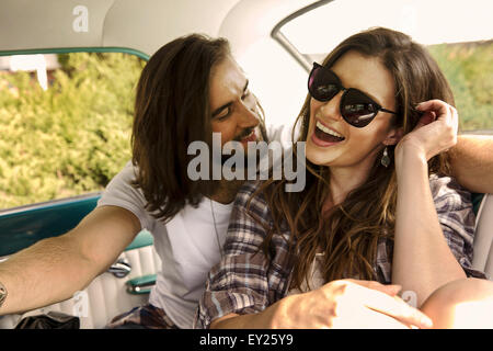 Young couple laughing in back seat of car - Stock Photo