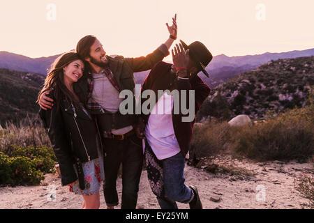 Three adult friends on desert road trip, Los Angeles, California, USA - Stock Photo