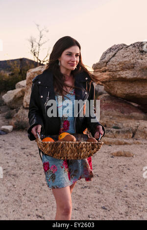 Young woman carrying basket of fruit for picnic in desert, Los Angeles, California, USA - Stock Photo