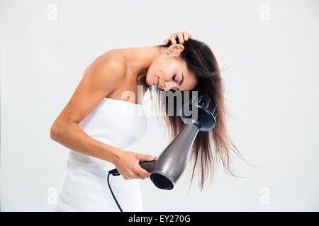 Young woman in towel drying her hair isolated on a white background - Stock Photo