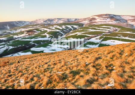Moon rising above moorland with traces of late winter snow. Beautiful colours of evening sunlight on the hillside. - Stock Photo
