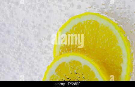 Slices of lemon in fizzy water - Stock Photo