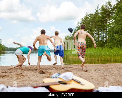 The group of the people runs in the lake, summer day - Stock Photo