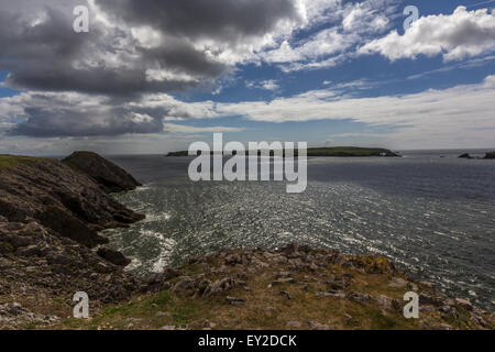 Coast line of South Wales with heavy clouds and blue sky with a rocky peninsular. - Stock Photo