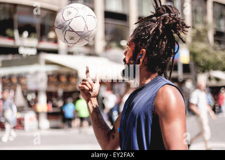 Young man doing balance tricks with his white and blue football in the center of Prague. - Stock Photo