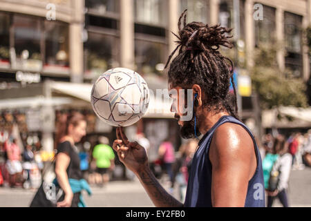 A young man doing football tricks on a main street in Prague. - Stock Photo