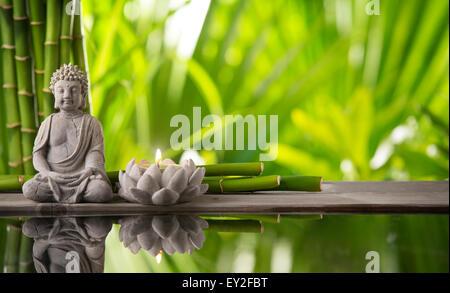 Buddha in meditation with burning candle - Stock Photo