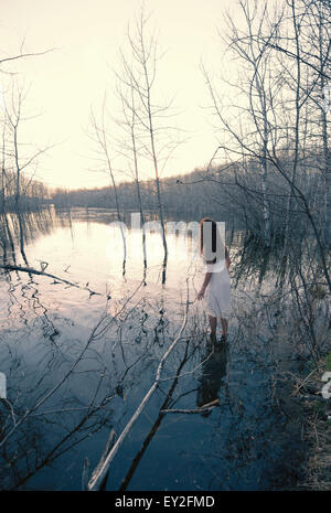A woman in a white dress standing in shallow water at dusk bya  lake shore. - Stock Photo