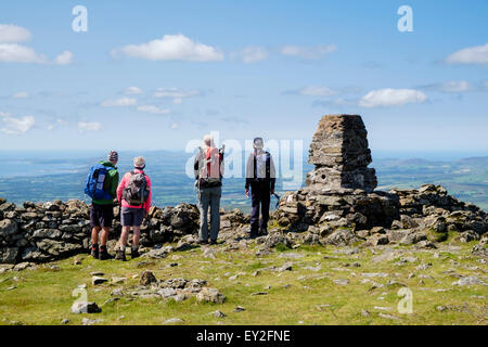 Four hikers looking west at view by trig point cairn on Moel Hebog mountain summit in mountains of Snowdonia Wales - Stock Photo