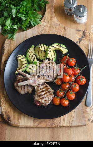 Lamb cutlets with avocado and tomatoes - Stock Photo
