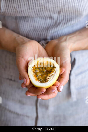 A woman holding half of a freshly cut passion fruit in her hands. - Stock Photo