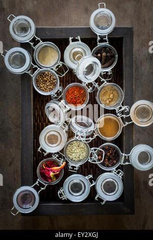 Spice jars in dark brown basket on dark wooden table. Top view - Stock Photo