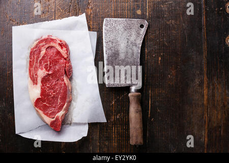 Raw fresh marbled meat Black Angus Steak and meat cleaver on dark wooden background - Stock Photo
