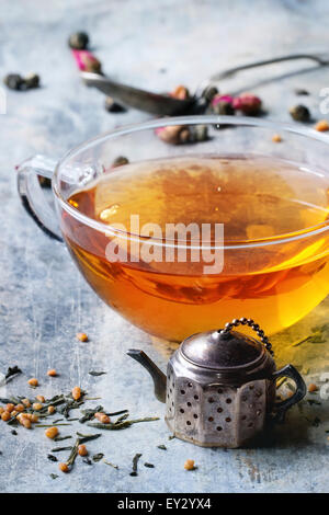 Vintage tea strainer as teapot and glass cup of hot tea with dry green tea leaves. Old tin backgtound. - Stock Photo