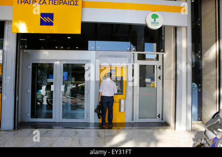 Athens, Greece. 20th July, 2015. A man withdraws cash from the ATM at a Piraeus Bank branch. Greek banks have re - Stock Photo