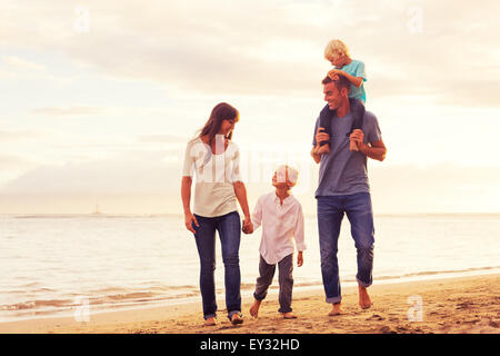 Happy young family having fun walking on the beach at sunset - Stock Photo