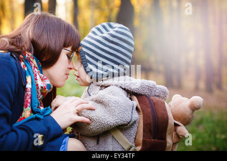 Young Happy Mother Talking to Son while Walking in the Park at the Day. Close up Portrait of Family. Copy Space - Stock Photo