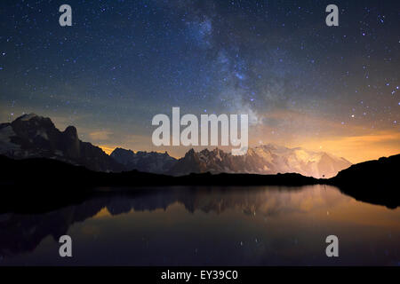 Mont Blanc massif at night with the Milky Way, reflected in Lac de Chésserys, Aiguilles de Chamonix on the left - Stock Photo