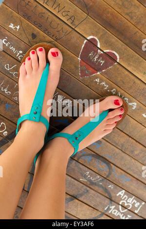 Female feet wearing turquoise sandals. - Stock Photo