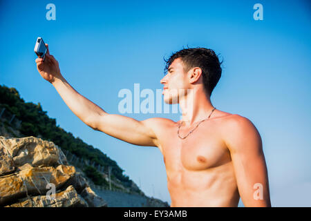 Side View of a Shirtless Young Man Taking Selfie Photos at the Beach While Sitting on Big Rock Under the Heat of - Stock Photo