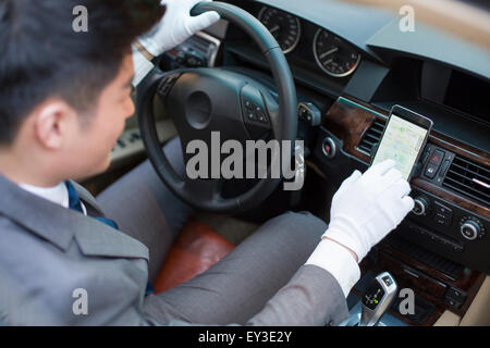 Chauffeur using smart phone as gps navigation for car - Stock Photo