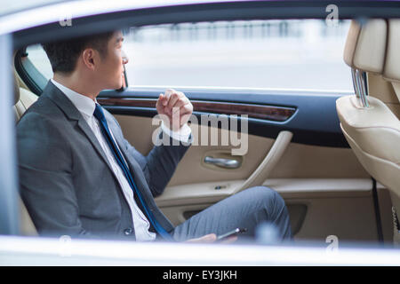 Businessman sitting in car back seat - Stock Photo