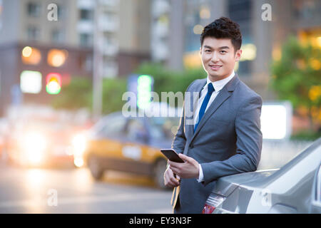 Businessman standing next to the car with smart phone - Stock Photo