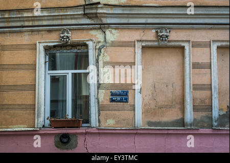 Cracked plastered wall windows and blue street sign details in central Tbilisi, Georgia, Eurasia.