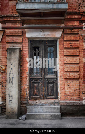 Stone steps leading up to old wooden doors on a property in Tbilisi, Georgia, Asia. - Stock Photo