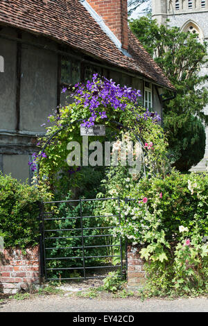 Lychgate cottage arch covered in clematis flowers at Hambleden,  Buckinghamshire, England - Stock Photo