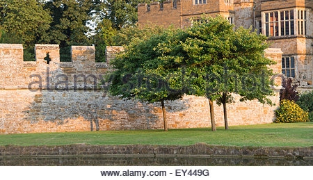 Trees and shadows on a wall at Broughton castle in the evening summer sunlight. Near Banbury, Oxfordshire, England - Stock Photo